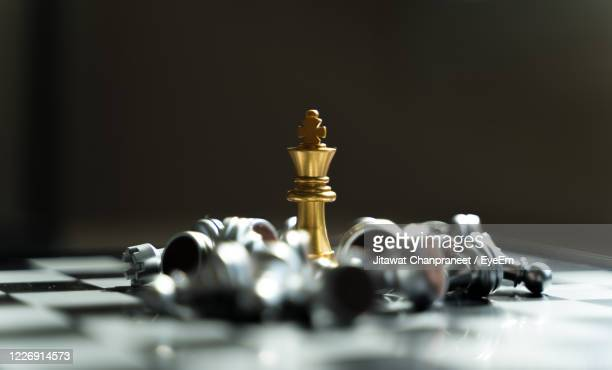 close-up of chess pieces on board against black background - chess stock pictures, royalty-free photos & images
