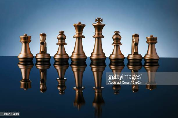 Close-Up Of Chess Pieces On Table Against Colored Background