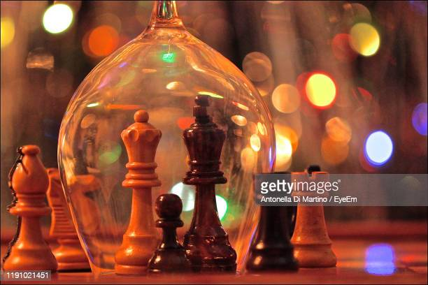 close-up of chess pieces on table against lights - antonella di martino foto e immagini stock