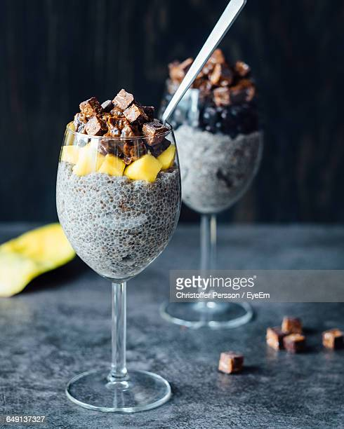 Close-Up Of Chia Pudding With Chocolates And Mango Slices On Table