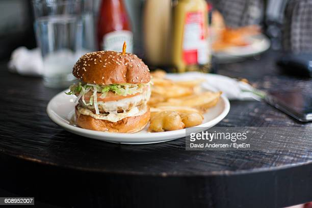Close-Up Of Chicken Burger With French Fries On Plate