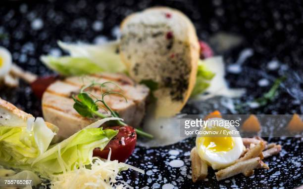 Close-Up Of Chicken Caesar Salad With Poached Egg Served In Plate