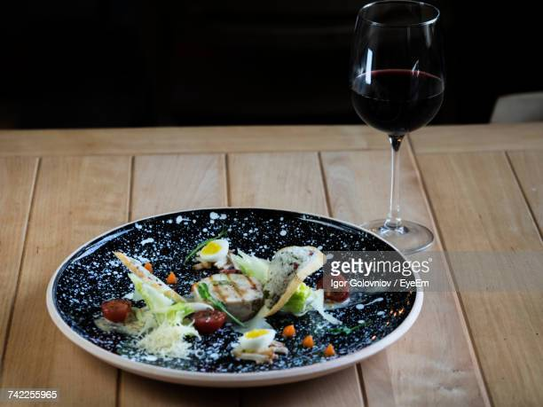Close-Up Of Chicken Caesar Salad With Poached Egg Served In Plate With Red Wine