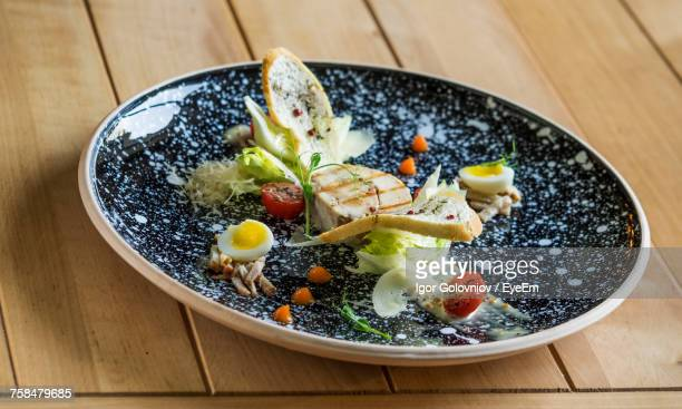 Close-Up Of Chicken Caesar Salad With Poached Eggs Served In Plate On Table