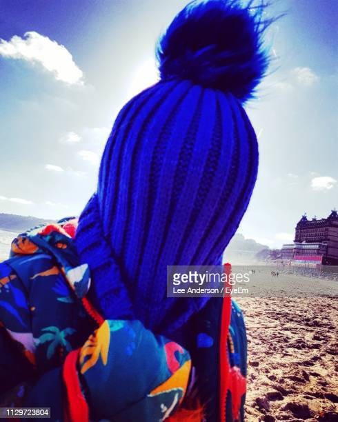 Close-Up Of Child Covering Face With Blue Knit Hat At Beach