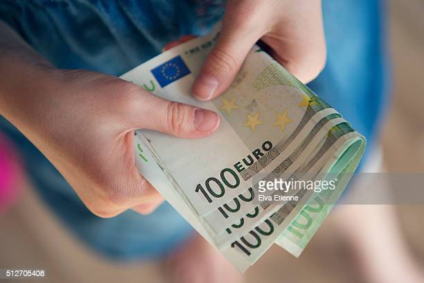 Close-up of child holding euro notes