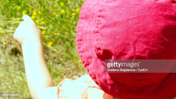 Close-Up Of Child Wearing Hat On Field During Sunny Day