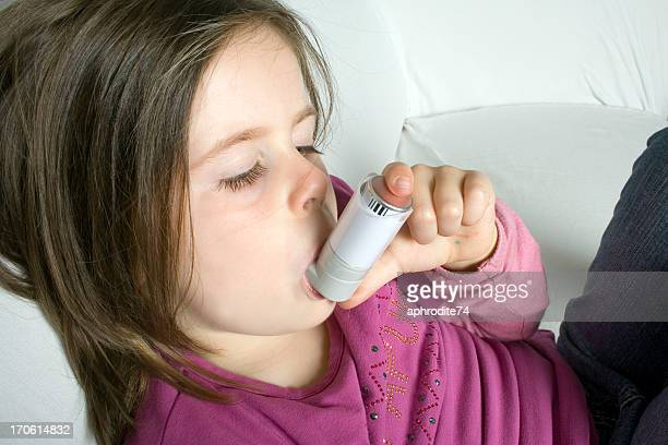 Close-up of child with asthma inhaler lying on the couch