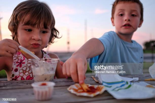 Close-Up Of Children Eating Outdoors