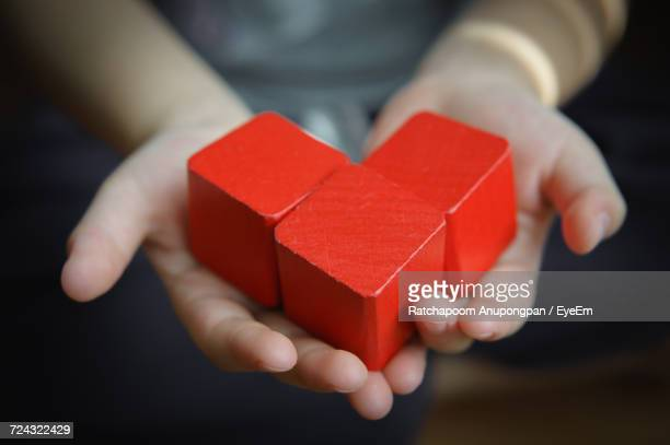 Close-Up Of Childs Hands Holding Red Blocks