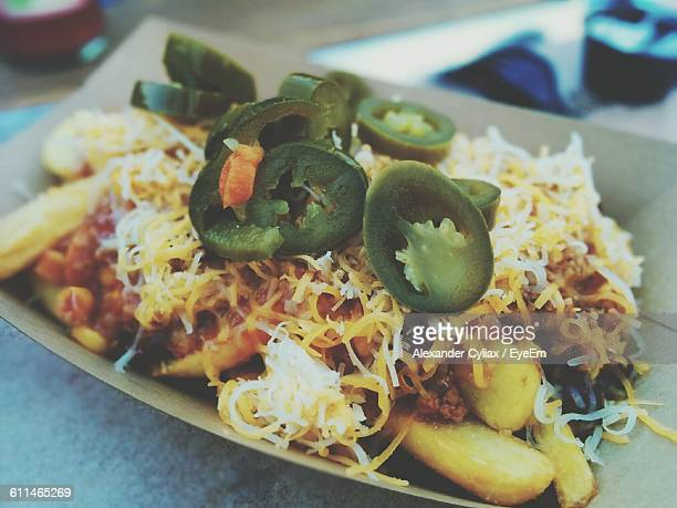 Close-Up Of Chili Fries With Shredded Cheese And Olives On Top