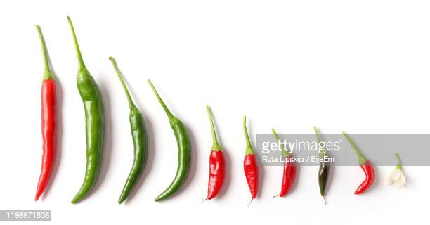 close-up of chili peppers against white background - green chili pepper stock pictures, royalty-free photos & images