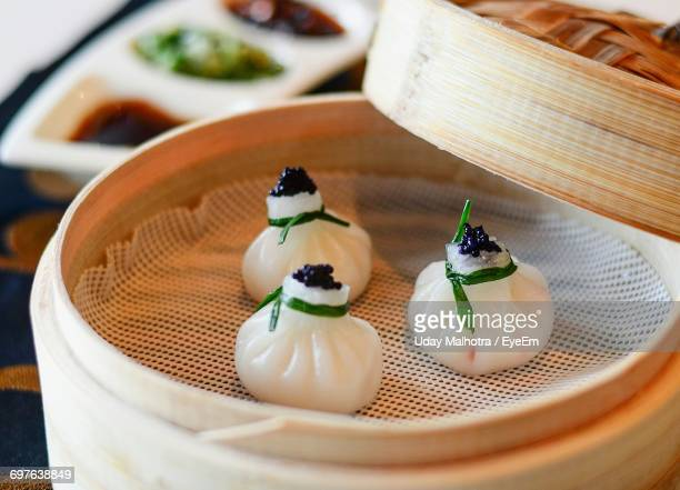 Close-Up Of Chinese Dumplings With Caviar In Bamboo Steamer On Table