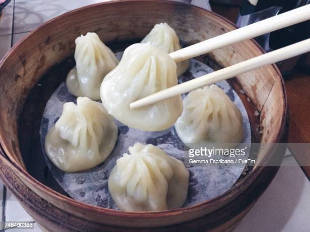 Close-Up Of Chinese Dumplings With Chopsticks Over Bamboo Steamer