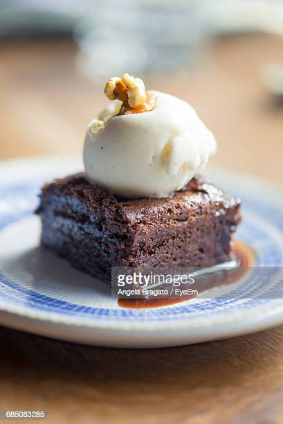 Close-Up Of Chocolate Brownie With Vanilla Ice Cream In Plate On Table