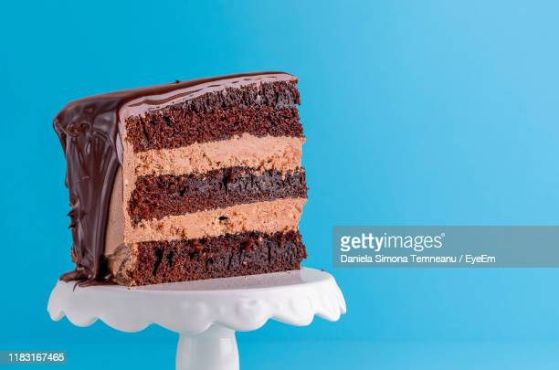 close-up of chocolate cake against blue background - chocolate cake stock pictures, royalty-free photos & images