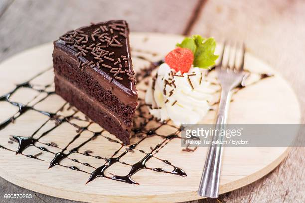 Close-Up Of Chocolate Cake With Fork On Cutting Board