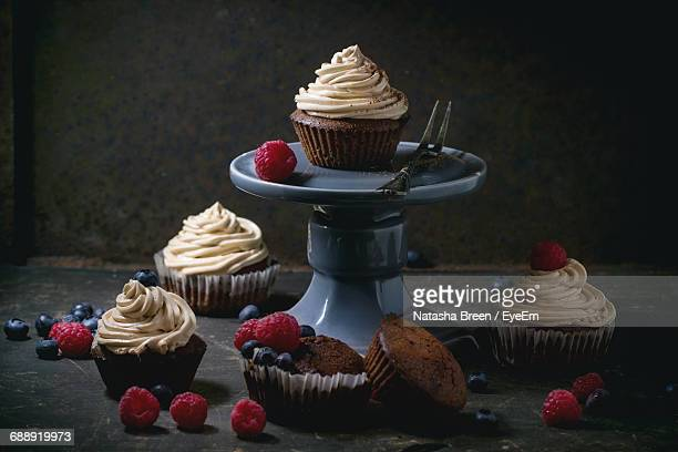 Close-Up Of Chocolate Cupcakes With Whipped Cream By Berries On Table