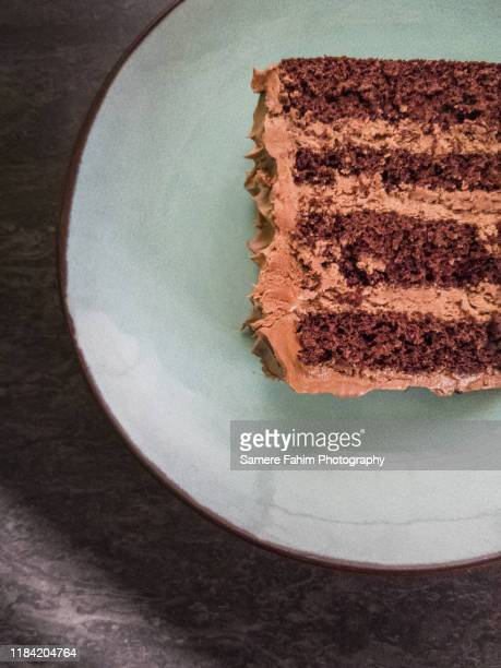 close-up of chocolate layer cake slice with buttercream on a plate - cakestand stock pictures, royalty-free photos & images
