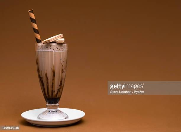close-up of chocolate milkshake in glass against brown background - milkshake imagens e fotografias de stock