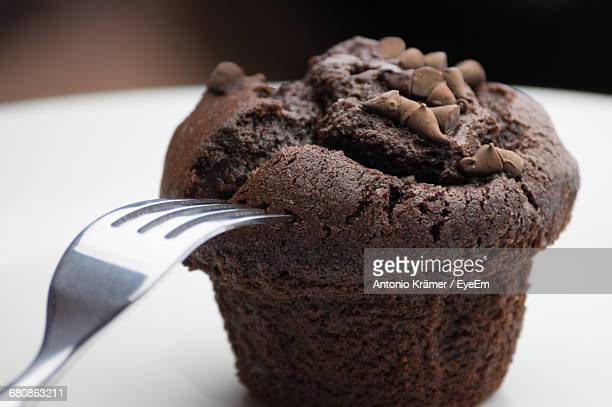 Close-Up Of Chocolate Muffin And Fork On Table