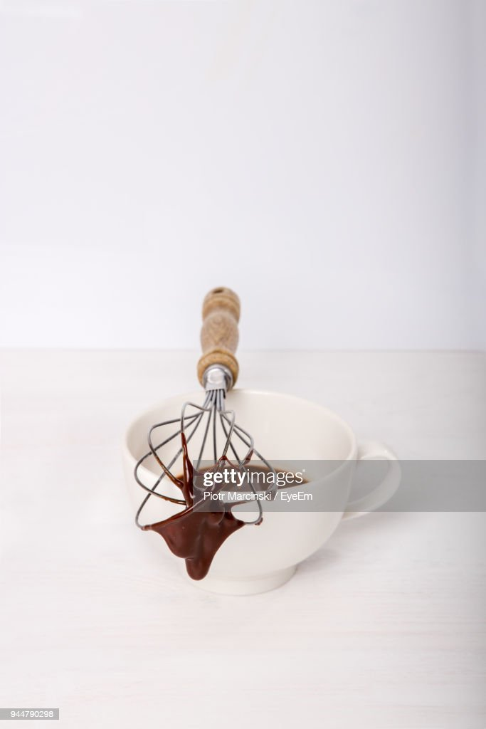 Close-Up Of Chocolate Sauce Dripping From Wire Whisk Against White Background : Stock Photo