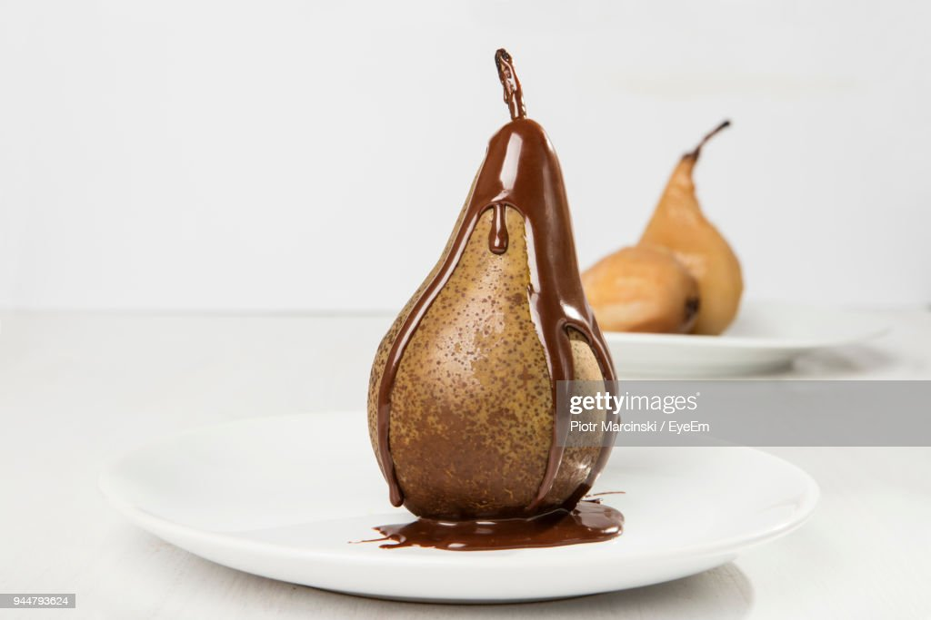 Close-Up Of Chocolate Sauce On Pear In Plate On Table Against White Background : Stock Photo