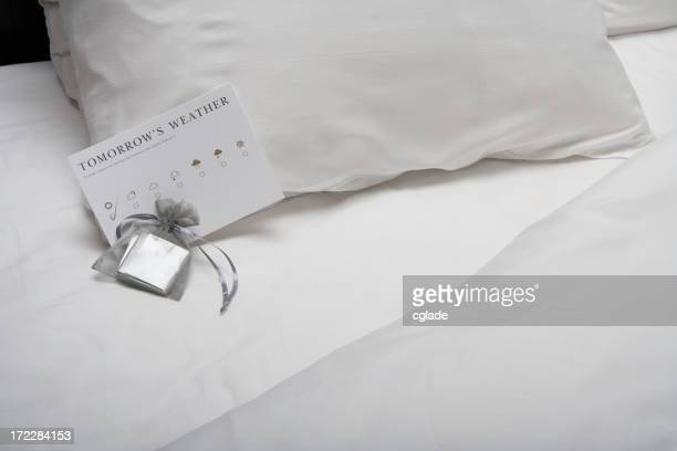 Close-up of chocolates on a turned-down hotel bed