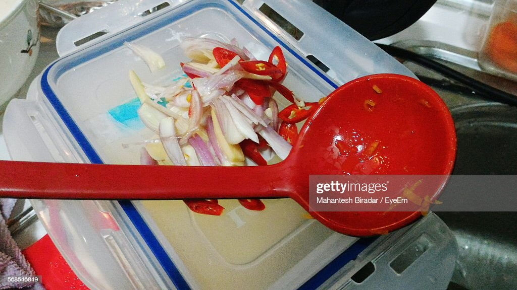 Close-Up Of Chopped Onions And Red Chili Peppers With Red Spoon On Lunch Box : Stock Photo