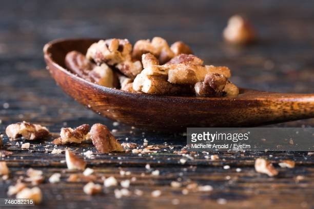 Close-Up Of Chopped Pecans In Wooden Spoon On Table