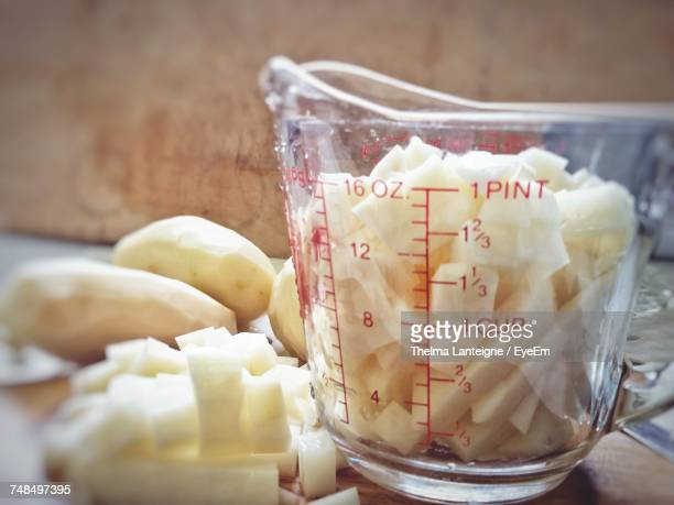 Close-Up Of Chopped Potatoes In Liquid Measure On Table