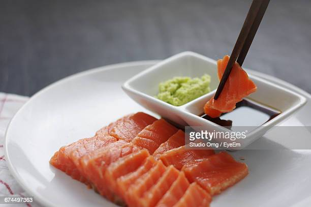 Close-Up Of Chopsticks Dipping Salmon Sushi In Soy Sauce
