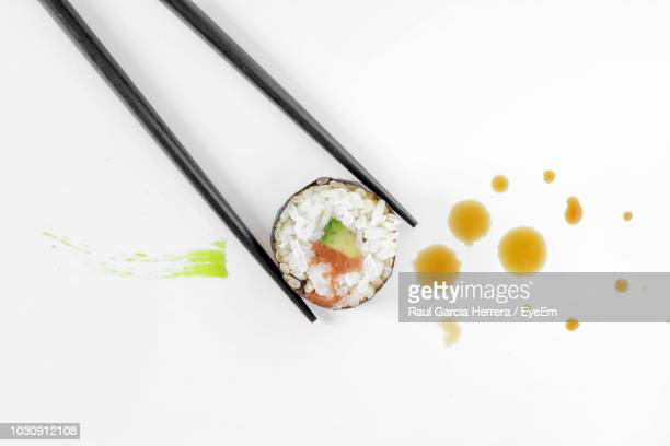 close-up of chopsticks holding sushi against white background - rich garcia stock-fotos und bilder