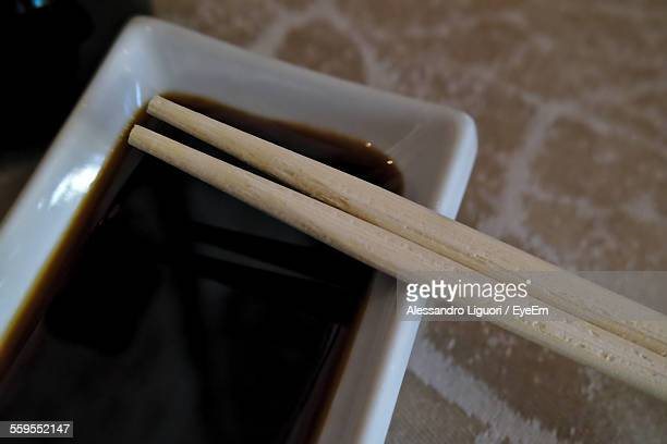 close-up of chopsticks on bowl of soy sauce - soy sauce stock pictures, royalty-free photos & images
