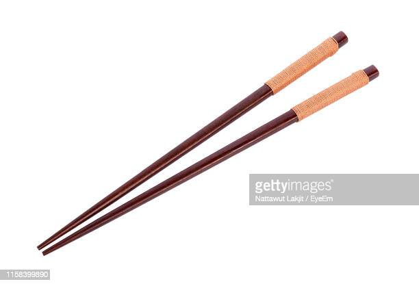close-up of chopsticks over white background - chopsticks stock pictures, royalty-free photos & images