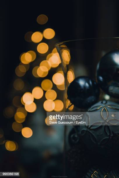 Close-Up Of Christmas Baubles In Glass Container Against Illuminated Lights