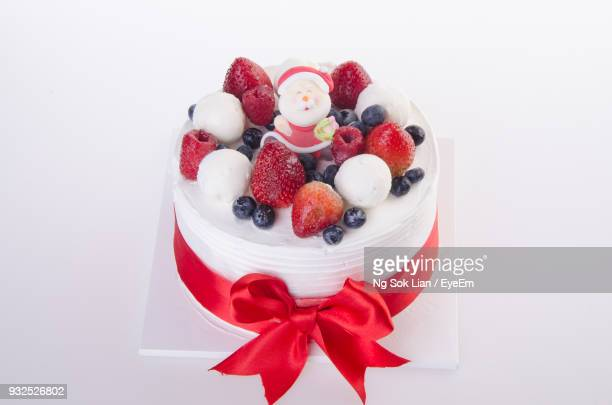 close-up of christmas cake over white background - christmas cake stock photos and pictures