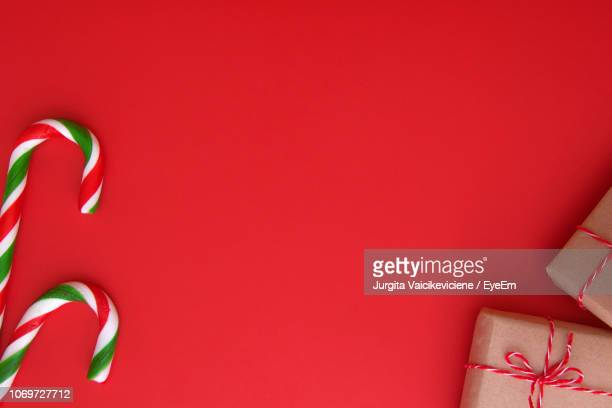 close-up of christmas decoration against red background - candy cane stock pictures, royalty-free photos & images