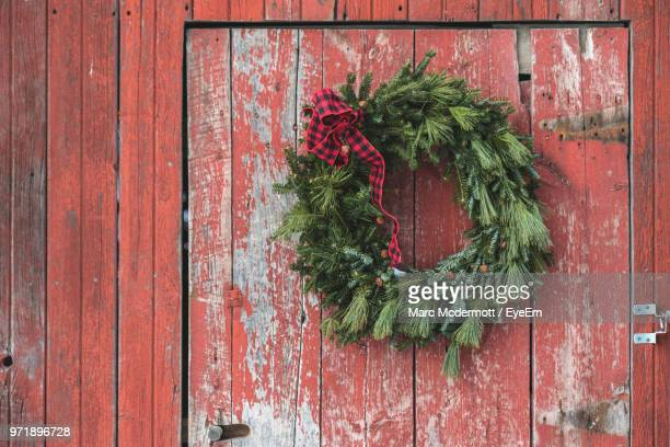 close-up of christmas decoration hanging against red door - wreath stock pictures, royalty-free photos & images