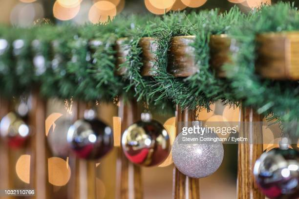 close-up of christmas decorations hanging on wood - steven cottingham stock-fotos und bilder
