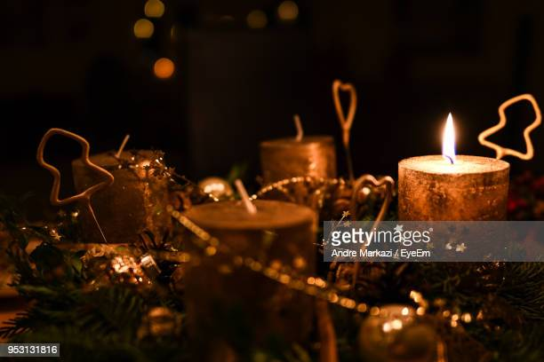 Close-Up Of Christmas Decorations With Burning Candles In Darkroom