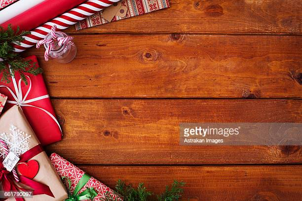 Close-up of Christmas gifts and wrapping papers on wooden table