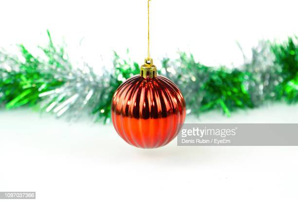 Close-Up Of Christmas Ornament With Tinsel Against White Background