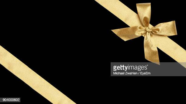 close-up of christmas present over black background - tied bow stock pictures, royalty-free photos & images