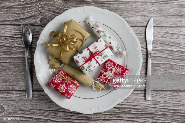 Close-Up Of Christmas Presents In Plate On Wooden Table