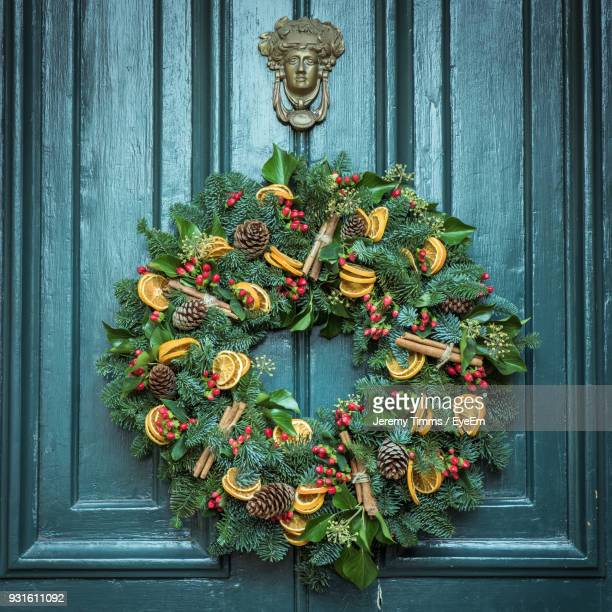 close-up of christmas wreath hanging on door - wreath stock pictures, royalty-free photos & images