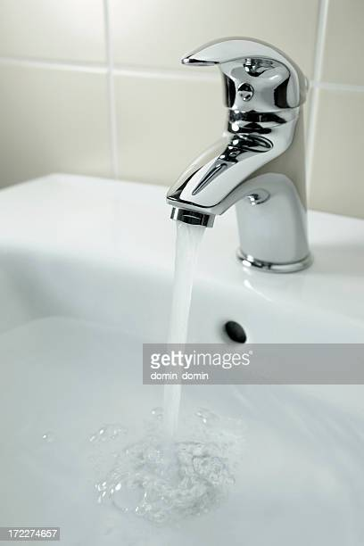 Close-up of chrome water tap with falling water, bathroom sink