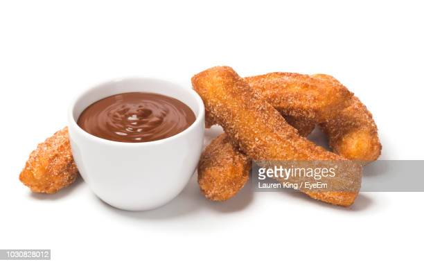 close-up of churros and dip against white background - churro stock photos and pictures