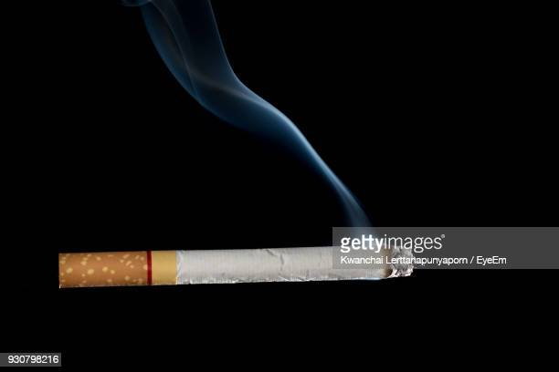 close-up of cigarette against black background - cigarette stock pictures, royalty-free photos & images
