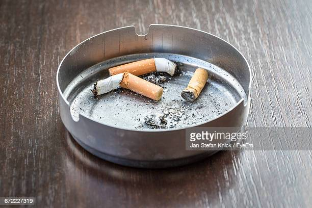 Close-Up Of Cigarette Butts In Ashtray At Table